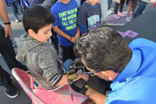 A student gets a Batman logo painted on his forearm during Date Elementary School's 20th anniversary celebration event on Dec. 1, 2017, which had nearly 800 students taking part in activities such as tic-tac-toe, musical chairs, bolo toss and a balloon-popping contest. (Photo courtesy of Fontana Unified School District)