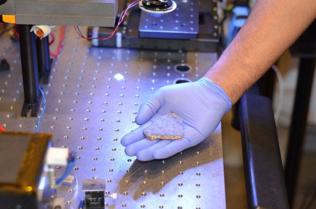 Rohit Bhartia of NASA's Mars 2020 mission holds a slice of a meteorite scientists have determined came from Mars. This slice will likely be used here on Earth for testing a laser instrument for NASA's Mars 2020 rover; a separate slice will go to Mars on the rover. (Courtesy of NASA/JPL