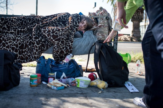 Teresa Rivera, a psychiatric social worker, who leads a Department of Mental Health mobile triage team, leaves a backpack with supplies for a young man who was sleeping on a bench along Sherman Way in Canoga Park on Monday, Feb. 5, 2018. The team provides outreach to homeless people with hopes of coaxing those with mental health needs to accept services and housing. (Photo by Sarah Reingewirtz, Pasadena Star-News/SCNG)