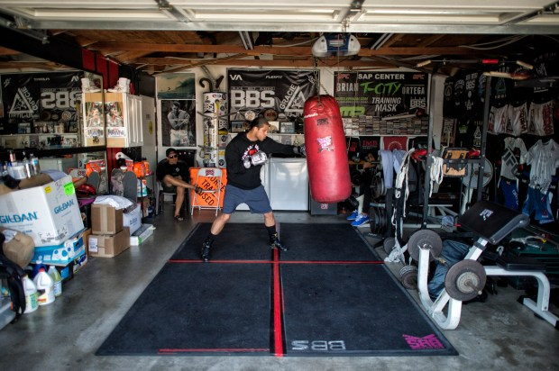 Brian Ortega works with coach James Luhrsen at Luhrsen's Harbor City home. Ortega fresh off a stunning second-round submission victory over Cub Swanson in December looks to stay unbeaten and possibly get a featherweight title shot when he takes on second-ranked former lightweight champion Frankie Edgar at UFC 222 in Las Vegas. (Hans Gutknecht, Los Angeles Daily News/SCNG)