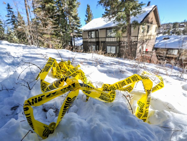 Sheriff's crime scene tape is left in the snow near a cabin on Club View Drive where fugitive ex-cop Christopher Dorner allegedly stayed for an unknown period of time while multiple law enforcement agencies searched the mountain area in Big Bear on Wednesday, Feb. 13, 2013. (Staff file photo by Rachel Luna, The Sun/SCNG)