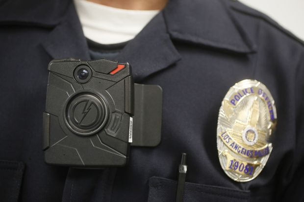 A Los Angeles Police officer wears an on-body cameras during a demonstration for media in Los Angeles Wednesday, Jan. 15, 2014. Police officers assigned to foot patrols of downtown Los Angeles began wearing the cameras on Wednesday as the city evaluates different models to include in its policing. (AP Photo/Damian Dovarganes)
