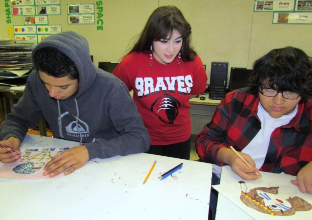 Noli Indian School art teacher Danielle Grass, center, discusses propaganda poster renderings by Art 2 students Damian Mariscal, left and Johnny Gomez. (Photo by Diane A. Rhodes, contributing photographer)