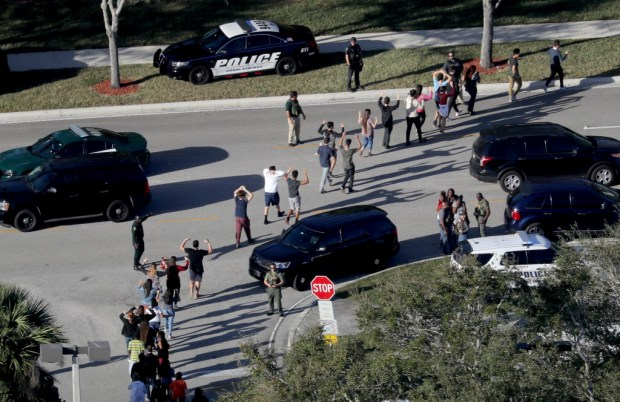 Students hold their hands in the air as they are evacuated by police from Marjorie Stoneman Douglas High School in Parkland, Fla., after a shooter opened fire on the campus. (Mike Stocker/South Florida Sun-Sentinel via AP)