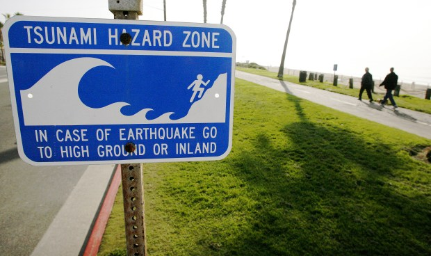 A tsunami warning sign, like the one here posted in Huntington Beach, line the coast. KEN STEINHARDT, THE ORANGE COUNTY REGISTER