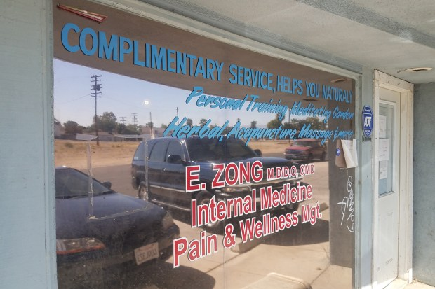 Dr. Edwin Zong closed his practice after the fatal shooting, leaving a handwritten notice on the door. He remains licensed to practice in good standing but says he won't return. Neighbors say patients still come by looking for him. (Brian Rinker for California Healthline)