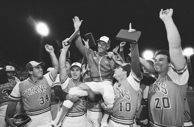 In this June 10, 1984, file photo, Cal State Fullerton coach Augie Garrido is lifted by his championship team after a 3-1 victory over Texas in the College World Series final in Omaha, Neb. Garrido, who won three national baseball championships at Cal State Fullerton and two more at Texas, died early Thursday at the age of 79. (AP Photo/File)