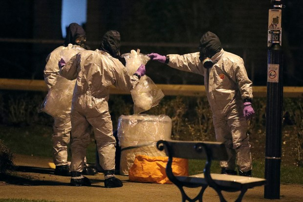 "Investigators in protective suits work at the scene in the Maltings shopping centre in Salisbury, England, Tuesday, March 13, 2018. The use of Russian-developed nerve agent Novichok to poison ex-spy Sergei Skripal and his daughter makes it ""highly likely"" that Russia was involved, British Prime Minister Theresa May said Monday. (Andrew Matthews/PA via AP)"