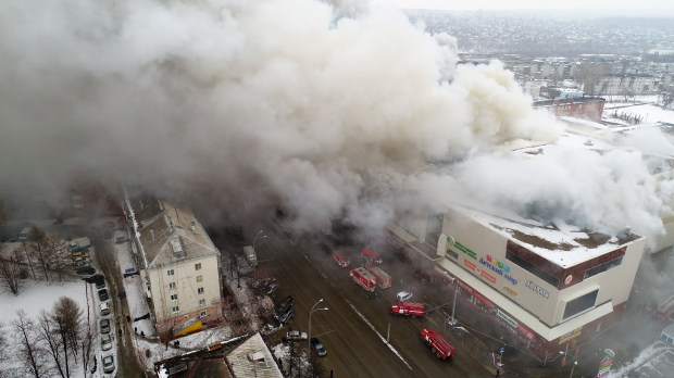 In this Russian Emergency Situations Ministry photo, on Sunday, March 25, 2018, smoke rises above a multi-story shopping center in the Siberian city of Kemerovo, about 3,000 kilometers (1,900 miles) east of Moscow, Russia. At least three children and a woman have died in a fire that broke out in a multi-story shopping center in the Siberian city of Kemerovo. (Russian Ministry for Emergency Situations photo via AP)