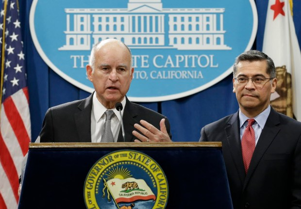 California Gov. Jerry Brown, left, accompanied by California Attorney General Xavier Becerra, listens to a question concerning remarks made U.S. Attorney General Jeff Sessions, Wednesday, March 7, 2018, in Sacramento, Calif. (AP Photo/Rich Pedroncelli)