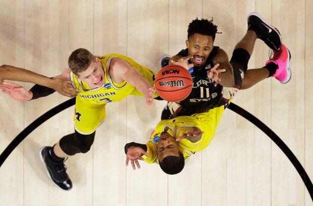 Florida State guard Braian Angola, top right, shoots against Michigan forward Moritz Wagner, left, and guard Muhammad-Ali Abdur-Rahkman during the first half of an NCAA men's college basketball tournament regional final Saturday, March 24, 2018, in Los Angeles. (AP Photo/Alex Gallardo)
