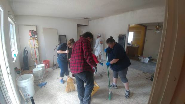 People gather to help clean up a house that was purchased through donated funds for Daniel Panico and Mona Kirk in Joshua Tree on March 10. The couple were arrested and charged with child abuse after they were found living squalid conditions. (Photo courtesy of Jackie Klear)