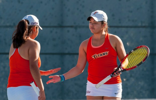 Cal State Fullerton's Sarah Nuno, left, and Karla Portalatin hand-slap after scoring during a doubles match in the season opener against UC San Diego in Fullerton on Thursday, Jan. 18, 2018. (Photo by Leonard Ortiz, Orange County Register/SCNG)