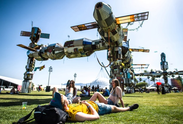 Festival-goers take a break underneath the Palm-3 World Station during the Coachella Valley Music and Arts Festival at the Empire Polo Club, in Indio, Calif. on Friday, April 13, 2018. (Photo by Watchara Phomicinda, The Press-Enterprise/SCNG)