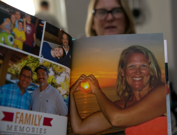 "Lisa Wittenberg holds a family photo album showing off pictures of herself doing things she loved -- hiking, being at the beach, hanging out with friends and family and living an active life. Wittenberg was diagnosed in August 2017 with ALS, a nervous system disease that weakens the muscles and is now confined to a wheelchair. ""This is totally not me,"" she says. (Photo by Mindy Schauer, Orange County Register/SCNG)"