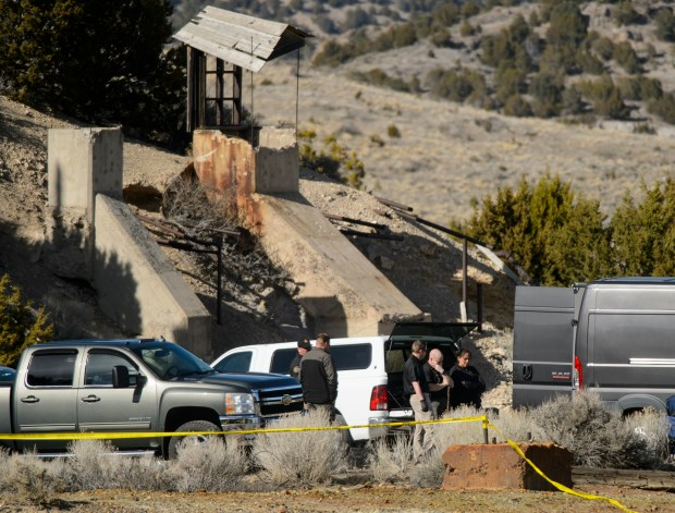 Law enforcement officials wait to load two bodies into a medical examiners truck after they were recovered from an abandoned mine in Utah's west desert near Eureka, Utah, Wednesday March 28, 2018. The two bodies found Wednesday in the abandoned mine are believed to be those of a teenage couple who disappeared months ago under suspicious circumstances, police said. (Steve Griffin/The Salt Lake Tribune via AP)
