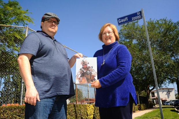 St. Martins in the Fields School teacher Susan Emslie and her son, Sean, stand near a sign on Gault Street that will become Joshua Cullins Way on May 17, 2018. Cullins was a Marine who was killed in Afghanistan in 2010. His two younger brothers attended the school, and he would come visit with the students when he was home between tours. He was also an LAPD officer. (Photo by Andy Holzman/Los Angeles Daily News)