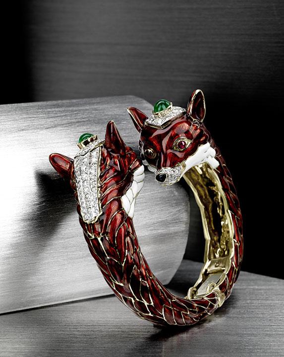 An enamel double fox head bangle with diamonds, emeralds and rubies by David Webb