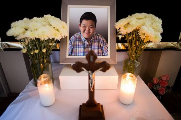 "A religious shrine was erected for Hun Joon ""Paul"" Lee, 19, who died last Friday as family and friends mourned his death the Lee's Whittier home on Monday, Sept. 14, 2015. Paul was found unresponsive in a parked bus and was pronounced dead at the Whittier Union High School District bus lot last Friday. (Photo by Watchara Phomicinda/ Whittier Daily News)"