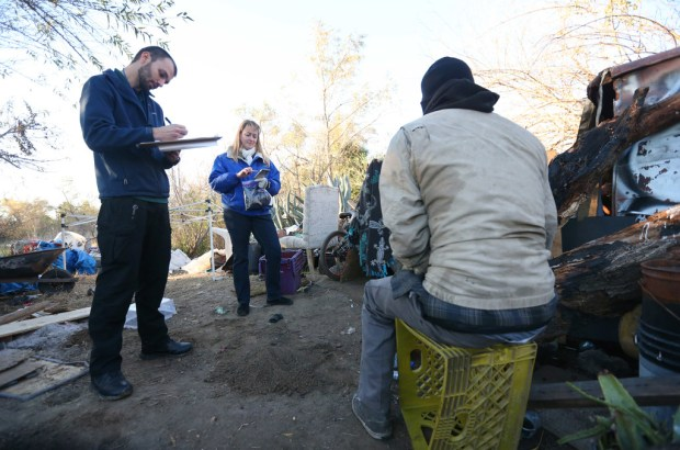Jacob Nuchols, a deputy for the Riverside County Probation Department , left, and Susan Von Zabern, Director of the Riverside County Department of Public Social Services, interview a homeless man living in a creek bed in Jurupa Valley on Tuesday, Jan. 23, 2018. (File photo by Stan Lim, The Press-Enterprise/SCNG)
