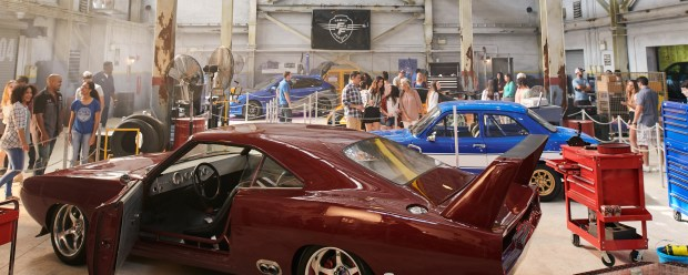Visitors walk by the cars on display as part of the Fast & Furious Supercharged attraction at Universal Orlando Resort.(Photo by Kevin Kolczyznski, Universal Orlando Resort)