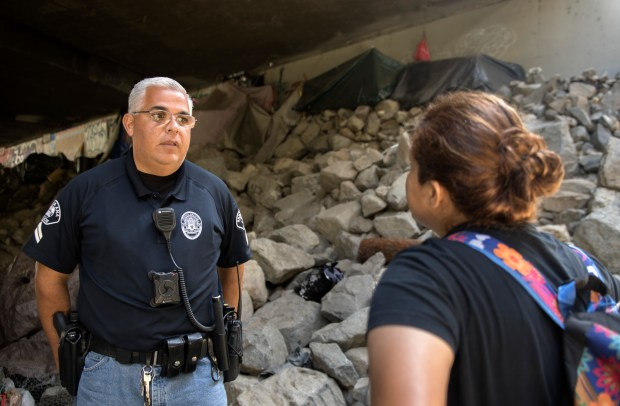 Santa Ana police Cpl. Juan Montiel asks a 35-year-old mother of two why she is back on the street instead of at home with her children and parents. She tells him she is just there to pick up some belongings. Montiel has built a rapport with the woman and her family. (Photo by Mindy Schauer, Orange County Register/SCNG)