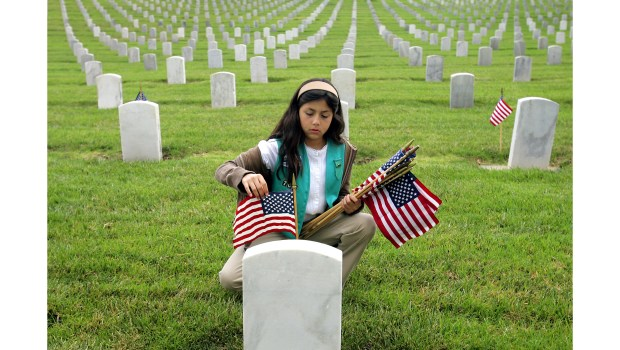 Girl Scout Jessica Ferrufino places flags at graves at Los Angeles National Cemetery.(File photo by Michael Owen Baker/Los Angeles Daily News)