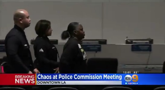 A woman is taken into custody Tuesday, May 8, 2018, during a meeting of the Los Angeles Police Commission after a powdery substance was thrown at Chief Charlie Beck. (Image from CBS2 video)