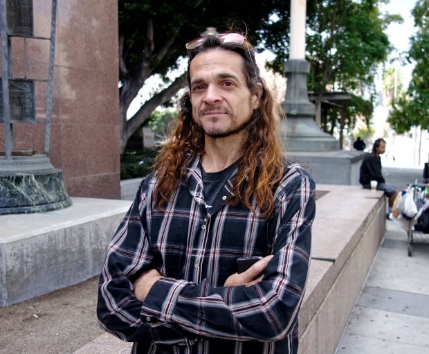Matthew Lentz, who says he was fathered by convicted murderer Charles Manson at an orgy, stands outside Los Angeles Superior Court Tuesday, May 8, 2018. He carried letters he said Manson sent him from prison and hoped to show them to a judge at a hearing over claims on Manson's estate. But he arrived too late for the hearing, and has until July 13 to show cause why he shouldn't be dismissed from the case. (AP Photo/Brian Melley)