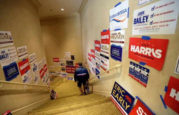 In this Saturday, May 5, 2018 photo, a man passes political posters during the California Republican Party convention in San Diego. California Republicans hoping to break a long losing streak are betting that anger over higher gas taxes and illegal immigration will give them an edge in races for governor and other marquee offices. (AP Photo/Gregory Bull)
