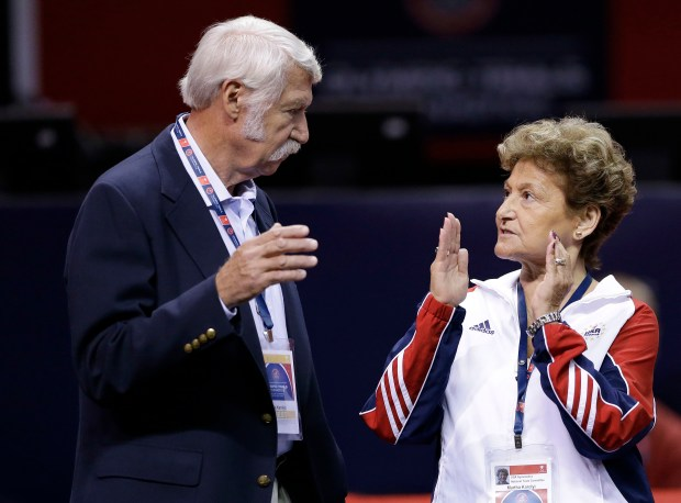 FILE - In this June 29, 2012, file photo, Bela Karolyi, left, and his wife Martha Karolyi talk on the arena floor before the start of the preliminary round of the women's Olympic gymnastics trials in San Jose, Calif. .(AP Photo/Gregory Bull, File)