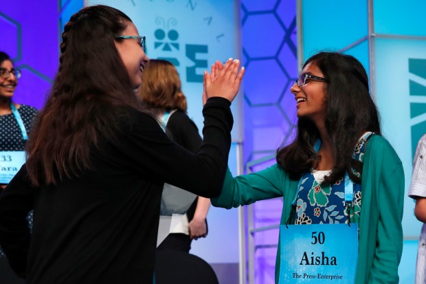 Enya Hubers, 12, from Burlington, Ontario, Canada, and Aisha Randhawa, 12, from Corona, Calif., high five after making it into the evening finals of the Scripps National Spelling Bee in Oxon Hill, Md., Thursday, May 31, 2018. (AP Photo/Jacquelyn Martin)