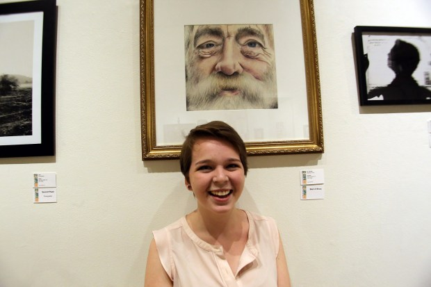 """Caroline Cook, a Vista Murrieta High School senior, poses with her drawing, """"Mr. Old Man,"""" that won Best in Show at The Press-Enterprise 56th Annual High School Art Show on Wednesday, May 16. (Photo by James Carbone, contributing photographer)"""