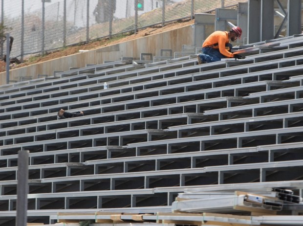 A worker puts finishing touches on the home bleachers at Canyon Springs High School on Wednesday, May 23. (Photo by Andrew Foulk, contributing photographer)
