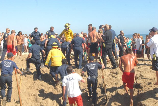 Newport Beach,Costa Mesa and Huntington Beach firefighters,Newport Beach lifeguards pull teenager from 7 foot sand hole , after a 29 minute rescue operation,at 54th Street and West Ocean Front, August 3, 2011. Photo by RICHARD KOEHLER FOR THE ORANGE COUNTY REGISTER/SCNG