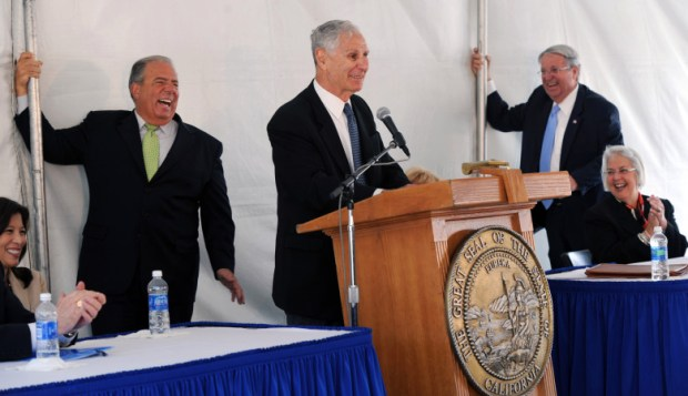 Former Mayor Bob Foster is among the people hanging on to tent poles as former California Governor George Deukmejian speaks as high winds erupting during groundbreaking for the new Gov. George Deukmejian Courthouse. (File photo)