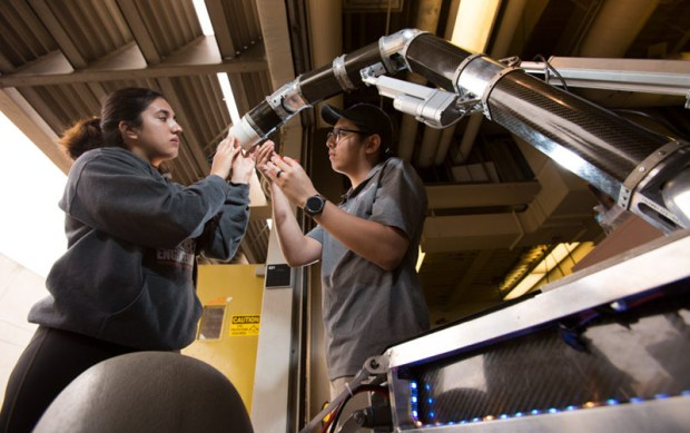 Students Dana Castro, left, and Ternel Enriquez put finishing touches on the Titan Rover's robotic arm.(Photo courtesy of Cal State Fullerton)