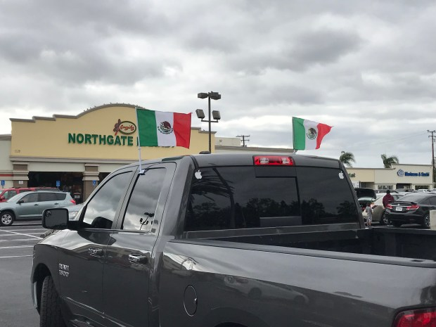A pickup displaying Mexican flags is seen at the Northgate González Market at 1120 S Bristol St. in Santa Ana on Sunday. Police on Sunday closed a portion of Bristol as fans of Mexico's soccer team celebrated Mexico's victory over Germany in the World Cup. Photo by Nathaniel Percy/Southern California News Group.