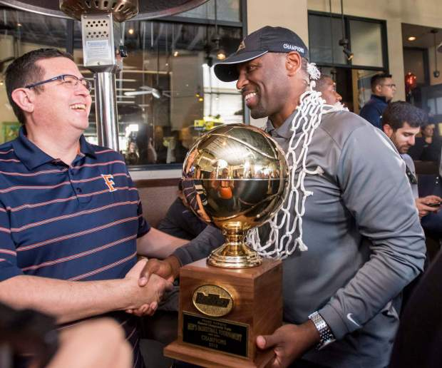 Cal State Fullerton basketball head coach Dedrique Taylor, right, gets congratulated as he enters an NCAA Tournament placement party at the Yard House restaurant in Brea on Sunday, Mar. 11, 2018. File photo basketball team, holds up the 2018 Frank Bowman Memorial Championship trophy as he The Titians will play Perdue in Detroit in the first round of the East Region on Friday (Photo by Leonard Ortiz, Orange County Register/SCNG)