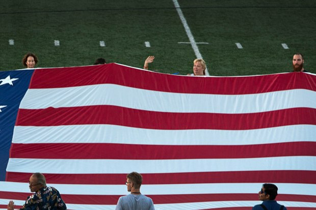 Attendants of Tustin's annual Fourth of July celebration wave a large US flag during the singing of the Star Spangled Banner at Tustin High School. The event will be held again this year. (Register file photo)
