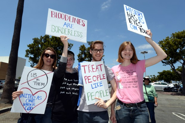 Tracy Pilger, left, her sons River and Blake, and Kayla Vokotek protest on Hawthorne Boulevard near the South Bay Galleria in Redondo Beach on Saturday, June 30, 2018, joining similar protests all over California and the nation to protest President Trump's immigration policies, particularly separating immigrant parents from their children. (Photo by Axel Koester, Contributing Photographer)