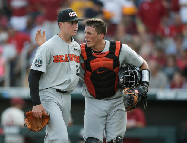 Oregon State pitcher Kevin Abel, left, is greeted by Oregon State catcher Adley Rutschman, right, after getting out of a bases-loaded jam during the third inning of Game 3 against Arkansas in the NCAA College World Series baseball finals, Thursday, June 28, 2018, in Omaha, Neb. (AP Photo/Nati Harnik)
