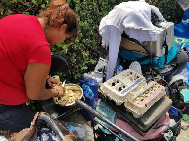 Nadine Lucero, 38, cuts up potatoes to make breakfast for herself and her friends after they were evicted from a homeless encampment near Pioneer Cemetery in San Bernardino. San Bernardino Police Quality of Life officers have received daily complaints about issues associated with homeless people in the area. (Photo by Beatriz E. Valenzuela)