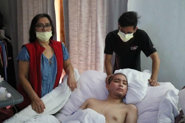 Clemente Salgado, Jr., acaricia en la cabeza a su hermano menor, Justin, quien convalece de un tumor cerebral que lo tiene postrado en cama, aunque aún así se pudo graduar de la secundaria.