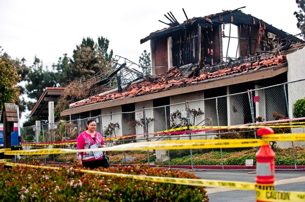 File photo of a women walking past the remains of the burnt down St. John Vianney Catholic Church in Hacienda Heights on Sunday morning, April 24, 2011. The church was destroyed by arson. (SGVN/Staff photo by Watchara Phomicinda/SVCity)