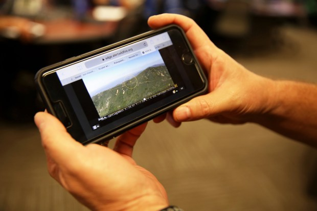 Troy Whitman, Fire Management officer for Southern California Edison, shows a live camera feed at Santiago Peak where he can monitor an SCE installation via his smartphone at SCE's 24-hour Emergency Operations and Situational Awareness Center in Irwindale, Calif. on Tuesday, June 19, 2018. The camera, installed for $100,00, allowed Whitman to follow the recent Santiago Fire near the 241 Freeway on his phone and see that there was no damage to SCE equipment. (Correspondent photo by Trevor Stamp)
