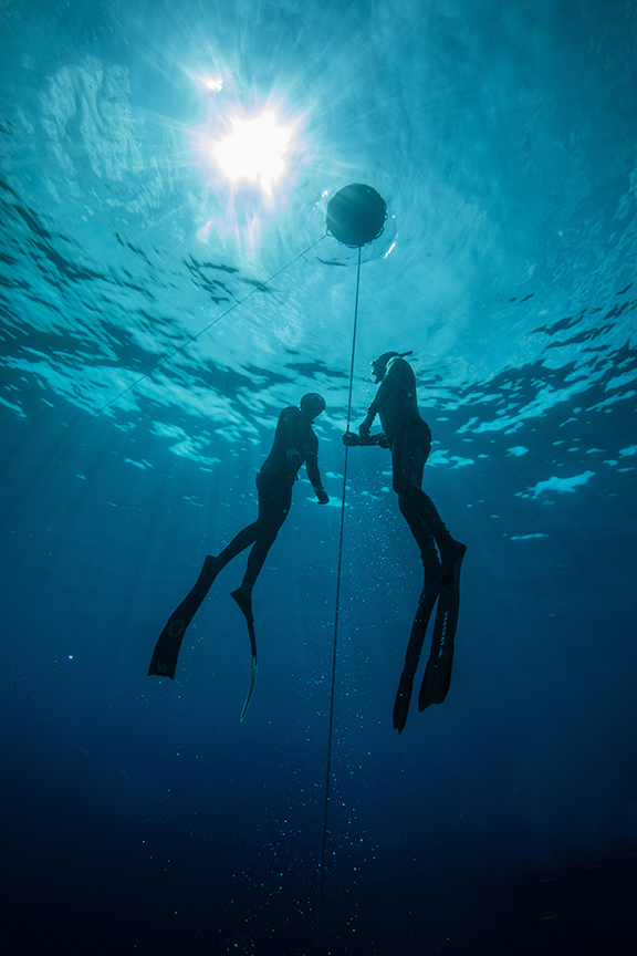Two freedivers train by diving down and up a line. Cory Fults, who has descended to 220 feet on a single breath, says training with a partner is essential.