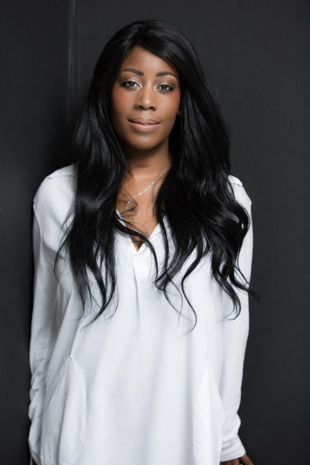 Author Natashia Deon standing, wearing a white blouse