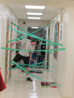 Student navigating a tape maze in a hallway