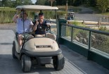 Two men in a golf cart driving over a bridge give the camera a thumbs up at the 2013 Howard F. Treiber Memorial Golf Outing